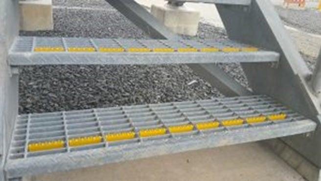 Close-up of U-Tred anti-slip stairnosings used on steel grate steps.
